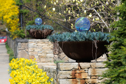 Flower pots with self-watering globes in a container garden